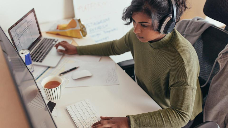 Female programmer coding on a desktop computer and laptop at her desk in office.