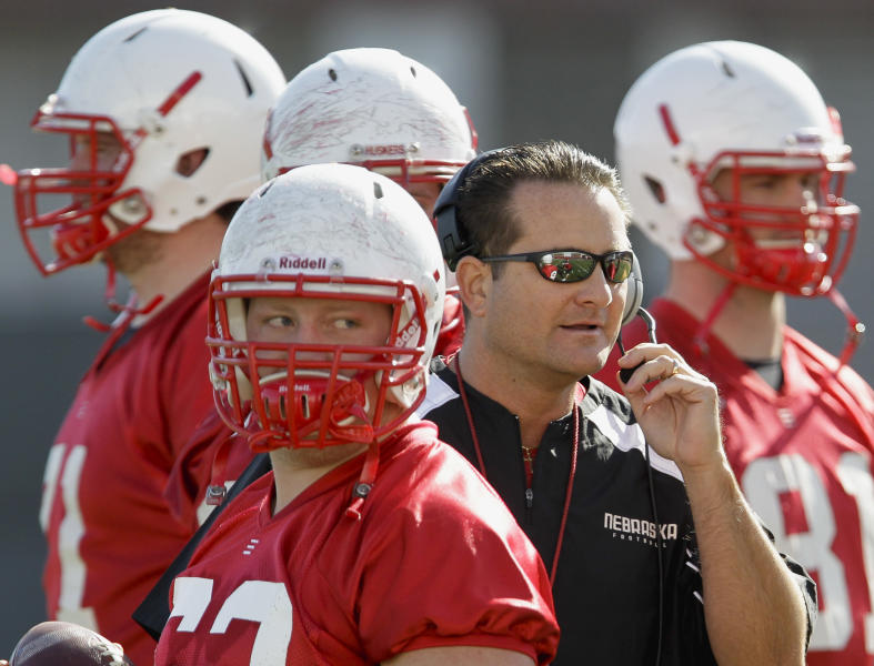 """FILE - In this March 10, 2012 file photo, Nebraska offensive coordinator Tim Beck works with players, including Ben Cotton, right and Ryan Klachko, center left, on the opening day of NCAA college football spring practice in Lincoln, Neb. Beck warns if the Cornhuskers have an emotional hangover from their 39-point Big Ten championship game loss, """"it's going to get ugly"""" when they play sixth-ranked Georgia in the Capital One Bowl.(AP Photo/Nati Harnik, File)"""