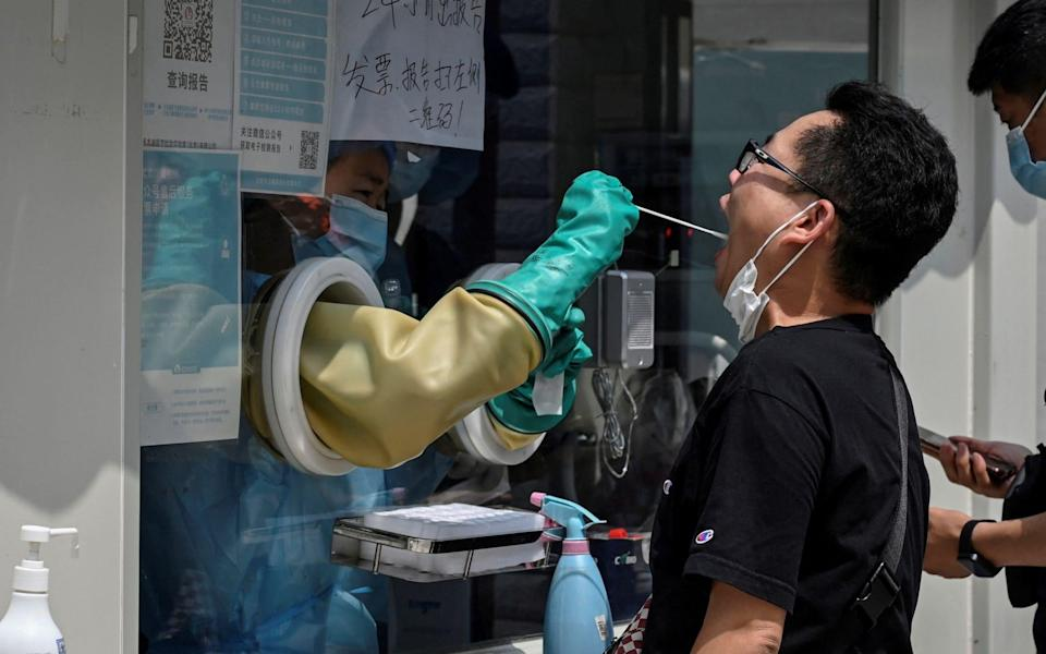 A health worker takes a swab sample from a man to be tested for Covid-19 coronavirus at a nucleic acid sample collection station in Beijing on August 4 - Jade Gao/AFP