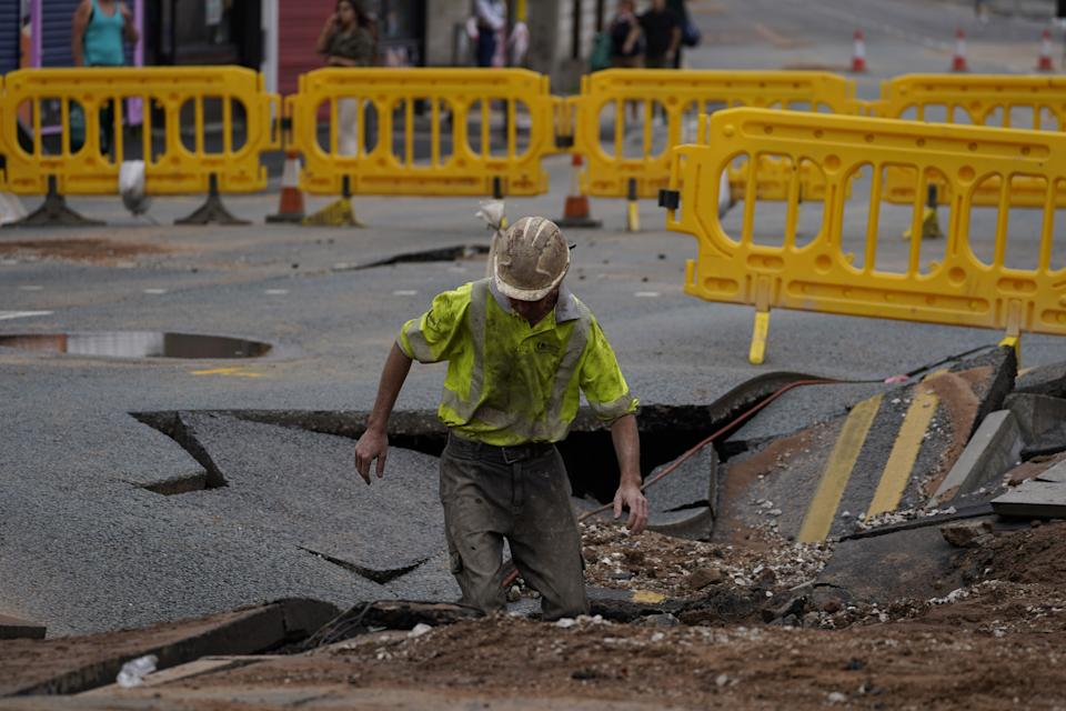 A United Utilities worker inspects a 4.5 metre (15ft) by six metre (20ft) sinkhole in Green Lane, Old Swan, Liverpool, caused by a suspected ruptured water main. Picture date: Saturday July 24, 2021.