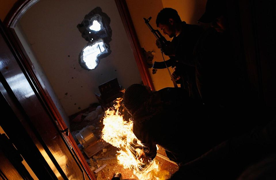 <p>Libyan rebel fighter rolls a burning tire into a room containing ensconced government loyalist troops who were firing on them during house-to-house fighting on Tripoli Street in downtown Misrata April 20, 2011 in Misrata, Libya. Rebel forces assaulted the downtown positions of troops loyal to Libyan strongman Moammar Gaddafi April 20, briefly forcing them back over a key bridge and trapping several in a building that fought back instead of surrendering, firing on the rebels in the building and seriously wounding two of them during the standoff. Fighting continued between Libyan government forces that had surrounded the city and anti-government rebels ensconced there. (Photo by Chris Hondros/Getty Images) </p>