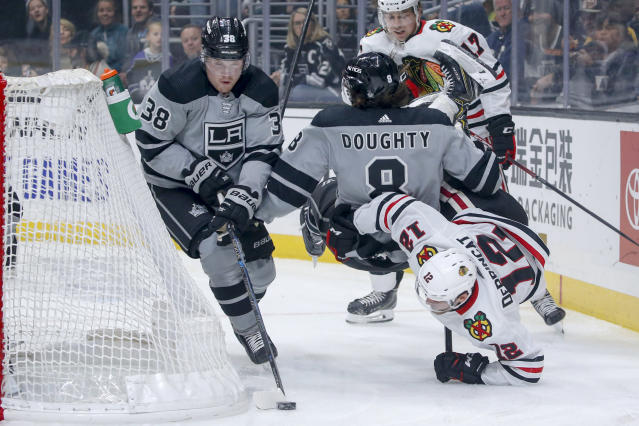 Los Angeles Kings forward Carl Grundstrom (38) controls the puck as defenseman Drew Doughty (8) collides with Chicago Blackhawks forward Alex DeBrincat (12) during the first period of an NHL hockey game Saturday, Nov. 2, 2019, in Los Angeles. (AP Photo/Ringo H.W. Chiu)