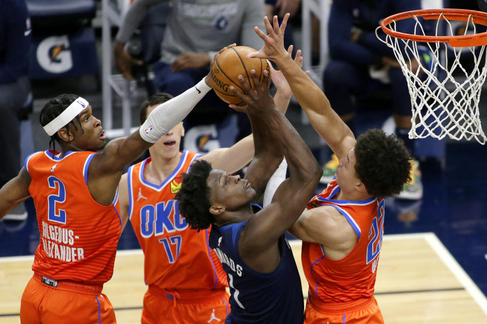 Minnesota Timberwolves forward Anthony Edwards (1) scores on Oklahoma City Thunder guard Shai Gilgeous-Alexander (2), forward Aleksej Pokusevski (17) and center Isaiah Roby (22) during the second quarter of an NBA basketball game Monday, March 22, 2021, in Minneapolis. (AP Photo/Andy Clayton-King)