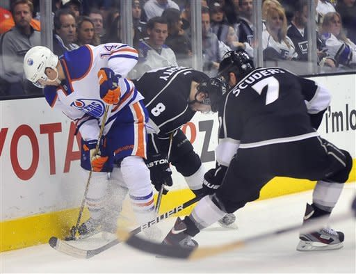 Edmonton Oilers's Jordan Eberle, left, works for the puck against Los Angeles Kings' Drew Doughty (8) and Rob Scuderi, right, during the second period of an NHL hockey game, Monday, April 2, 2012, in Los Angeles. (AP Photo/Richard Hartog)