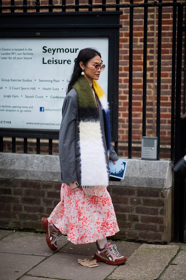 <p>Hang your colorblock scarf evenly over the lapels of your blazer and let both sides hang. You can add a funky twist by pulling on a printed midi skirt that reveals a hint of your sneakers and socks underneath. </p>