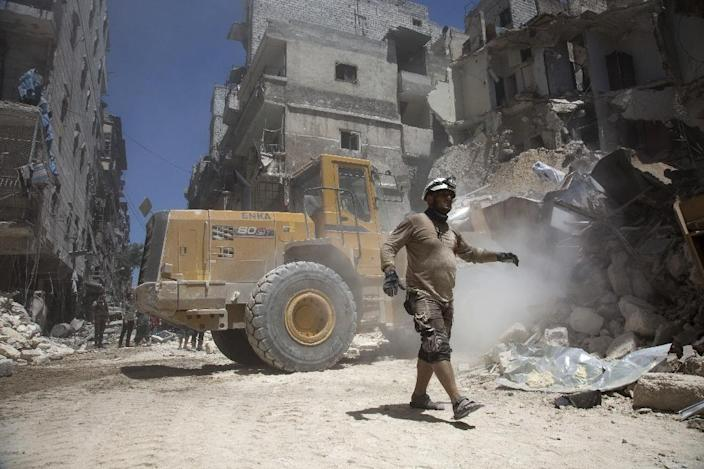 Syrian rescue workers clear rubble in the war-shattered city of Aleppo on July 26, 2016 (AFP Photo/Karam al-Masri)