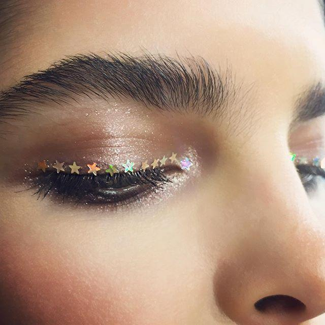 <p>Makeup artist Michael Anthony put a 3D spin on eye statements, sticking small holographic stars along the lashline to accent a shimmery beige smoky eye.</p>