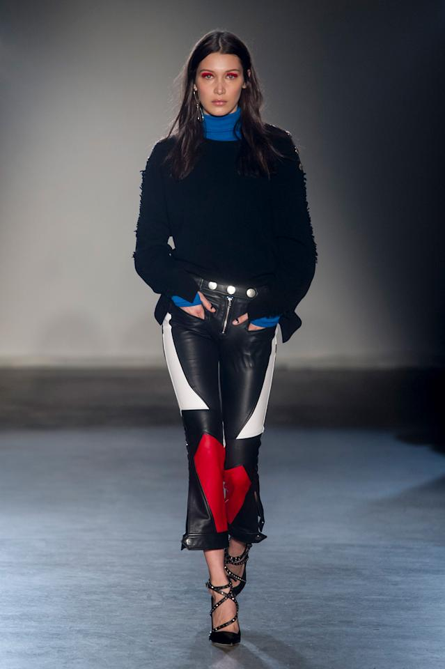 <p>Bella opens the show in a star-studded outfit, wearing leather trousers with red and white patterns and a blue turtleneck. (Photo: ImaxTree) </p>