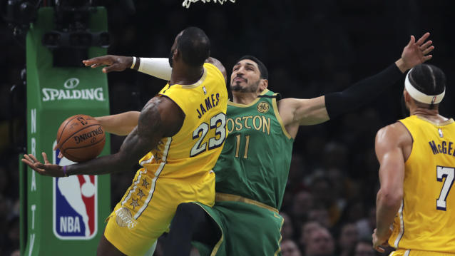 Boston Celtics center Enes Kanter (11) blocks the ball as he stops a drive to the basket by Los Angeles Lakers forward LeBron James (23) during the first half of an NBA basketball game in Boston, Monday, Jan. 20, 2020. The Celtics defeated the Lakers 139-107. (AP Photo/Charles Krupa)