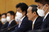 Japanese Prime Minister Yoshihide Suga, second right, declares a state of emergency for Tokyo and three other prefectures during the government task force meeting for the COVID-19 measures at the prime minister's office Friday, April 23, 2021, in Tokyo. (AP Photo/Eugene Hoshiko, Pool)