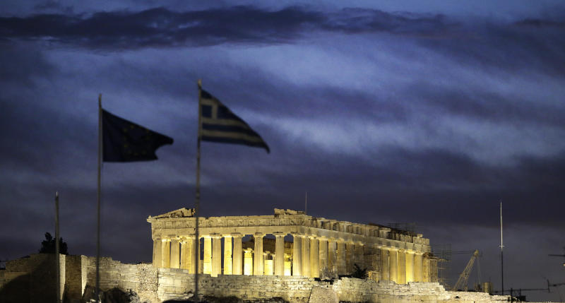 The Greek and European Union flags wave above the Ministry of Finance as the illuminated temple of Parthenon is seen during the sunset in Athens on Monday, Oct. 8, 2012 prior to a union anti-austerity rally a day before the visit by German Chancellor Angela Merkel. The authorities are keen to prevent embarrassing riots. More than 7,000 police will be on security duty in the capital from early Tuesday, while public gatherings will be banned in much of the city center and on a 100-meter (yard) radius from the route her motorcade will follow. The ban will not affect the main protests, but will prevent demonstrators from reaching the German embassy, where a populist right wing party was planning a protest. (AP Photo/Dimitri Messinis)