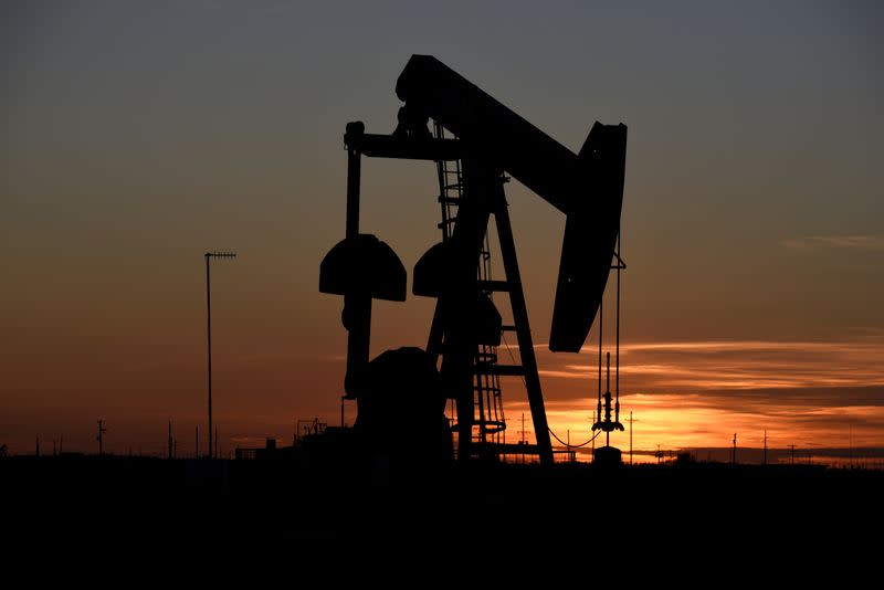 A pump jack operates at sunset in an oil field in Midland
