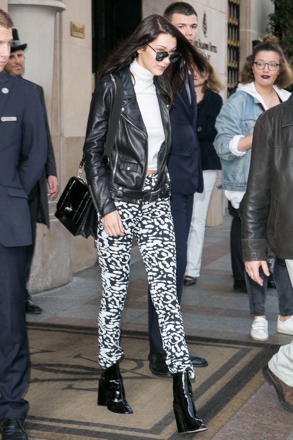 <p>In black and white printed leggings, a white turtleneck, black leather motorcycle jacket, patent leather booties, reflective sunglasses and a structured black handbag while out in Paris. </p>
