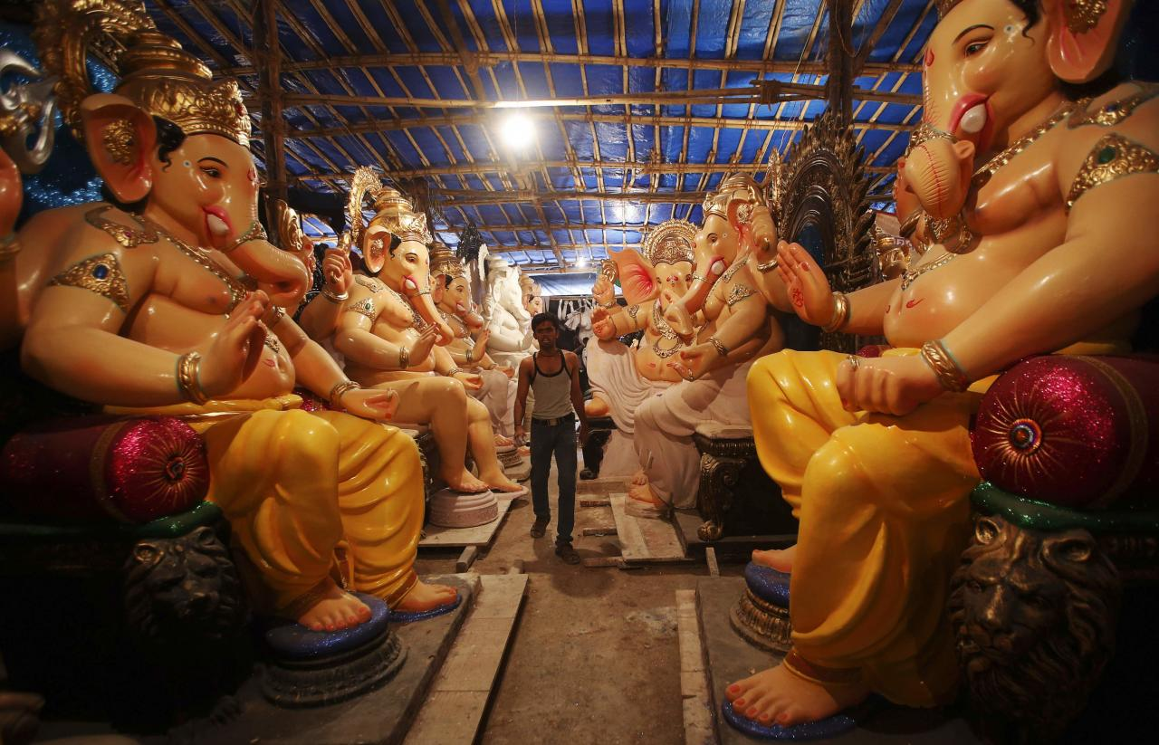 "An artisan walks past the idols of Hindu elephant god Ganesh, the deity of prosperity, kept inside a workshop in Mumbai September 3, 2013. The idols will be paraded through the streets in a procession during the Ganesh Chaturthi festival, accompanied by dancing and singing. They will then be immersed in a river or the sea symbolizing a ritual send-off of Ganesh's journey towards his abode in ""Kailash"", while taking away with him the misfortunes of all mankind. The festival will be celebrated on September 9. REUTERS/Danish Siddiqui (INDIA - Tags: SOCIETY RELIGION)"