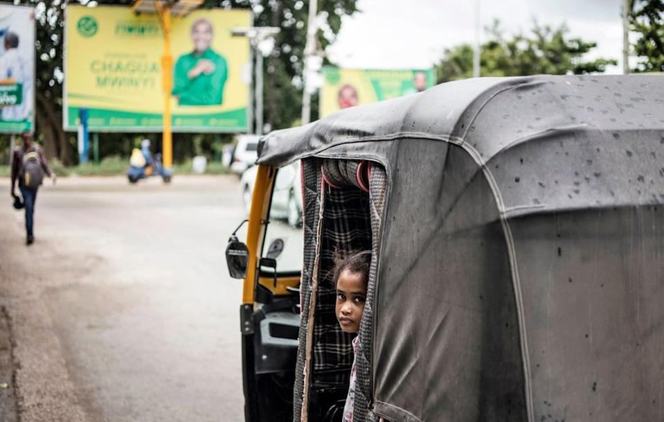 A girls peeks out from a tuk-tuk at a busy intersection in front of electoral posters for the Tanzanian ruling party Chama Cha Mapinduzi in Stone Town, Zanzibar, on October 26, 2020.