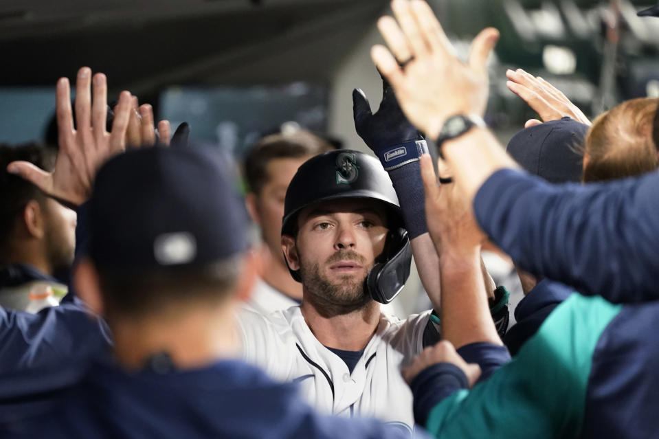 Seattle Mariners' Mitch Haniger is congratulated on his solo home run against the Texas Rangers during the eighth inning of a baseball game Saturday, May 29, 2021, in Seattle. (AP Photo/Elaine Thompson)