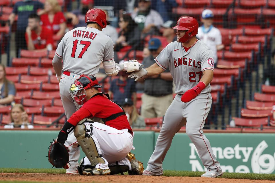 Los Angeles Angels' Shohei Ohtani (17) celebrates his two-run home run that also drove in Mike Trout (27) as Boston Red Sox's Christian Vazquez kneels at home plate during the ninth inning of a baseball game, Sunday, May 16, 2021, in Boston. (AP Photo/Michael Dwyer)