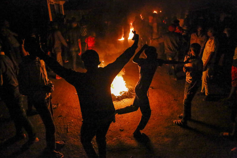 In this photo taken Monday, June 1, 2020, residents burn fires late at night on a street to protest the death of James Mureithi, a homeless man who protesters alleged was shot dead by police during the nightly dusk-to-dawn curfew established to curb the spread of the coronavirus, in the Mathare slum, or informal settlement, of Nairobi, Kenya. Hundreds of people in Mathare left their homes and burnt tires on the streets in the latest outrage over alleged police brutality, with a rights activist claiming that 19 Kenyans from low-income neighborhood have died from police actions in enforcing the curfew. (AP Photo/Brian Inganga)