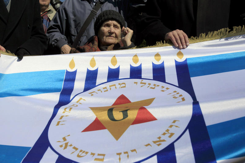 "Survivor of the camps, Zana Santicario-Saatsoglou is seen behind a banner that reads in Hebrew :""The organization of death camps survivors from Greece in Israel"" in the northern port city , of Thessaloniki, Greece, on Saturday, March 16, 2013. Jewish residents in this northern Greek city have gathered to commemorate the 70th anniversary from the first roundup and deportation of Jews to Nazi extermination camps in World War II. By August 1943, 46,091 Jews had been deported to Auschwitz-Birkenau. Of those, 1,950 survived. (AP Photo/Nikolas Giakoumidis)"
