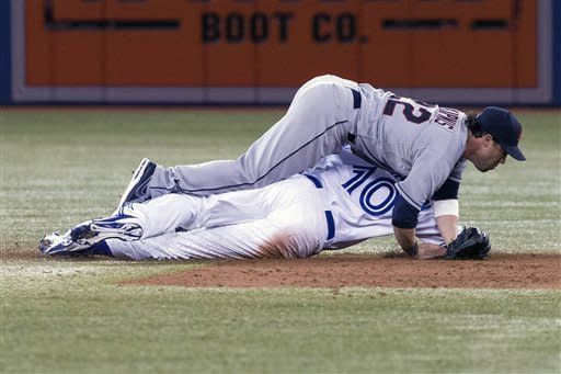 Cleveland Indians second baseman Jason Kipnis tumbles onto Toronto Blue Jays' Edwin Encarnacion during a double play in the third inning of a baseball game in Toronto on Tuesday April 2 , 2013. (AP Photo/The Canadian Press, Chris Young)