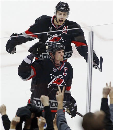 Carolina Hurricanes' Eric Staal (12) celebrates his game-winning overtime goal with Brandon Sutter (16) during an NHL hockey game against the Toronto Maple Leafs in Raleigh, N.C., Thursday, Dec. 29, 2011. The Hurricanes won 4-3. (AP Photo/Karl B DeBlaker)