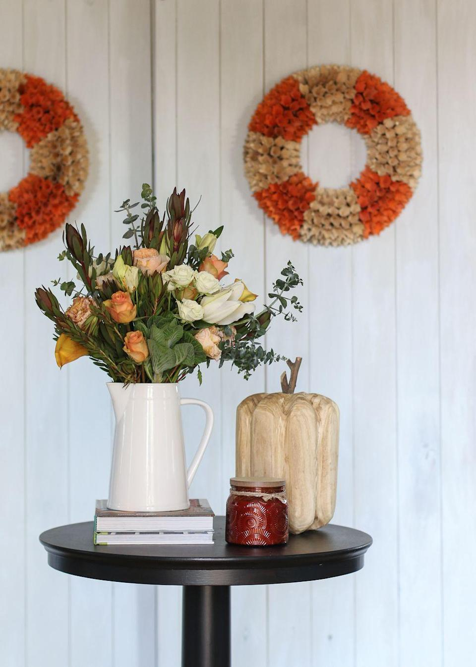 """<p>On white wood walls, blogger Michael Wurm Jr. of <a href=""""http://inspiredbycharm.com/2016/09/fall-entertaining-around-my-house-tour.html"""" rel=""""nofollow noopener"""" target=""""_blank"""" data-ylk=""""slk:Inspired by Charm"""" class=""""link rapid-noclick-resp"""">Inspired by Charm</a> decorated his <a href=""""https://www.elledecor.com/shopping/furniture/g9872267/entryway-tables/"""" rel=""""nofollow noopener"""" target=""""_blank"""" data-ylk=""""slk:entryway"""" class=""""link rapid-noclick-resp"""">entryway</a> for fall with two matching wreaths. Guests are greeted by a rose-filled floral arrangement in an array of autumn shades, and a carved wooden pumpkin. </p>"""