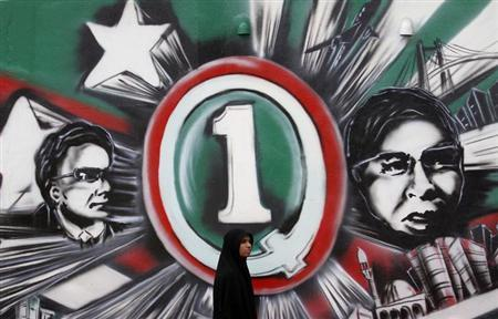 A Muslim woman walks past a painted wall of Maldives presidential candidates Gasim Ibrahim (R) and Hassan Saeed in Male September 6, 2013.