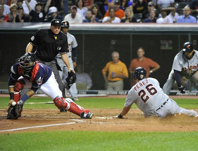 Detroit Tigers base runner Hernan Perez slides safely into home plate as Cleveland Indians catcher Carlos Santana fields the throw during the fifth inning of a baseball game at Progressive Field in Cleveland, Thursday, Aug. 8, 2013. Watching the play is home plate umpire Ron Kulpa and Tigers' Prince Fielder. (AP Photo/Phil Long)