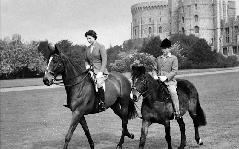 The Queen riding with Prince Charles in the park of Windsor Castle - AFP