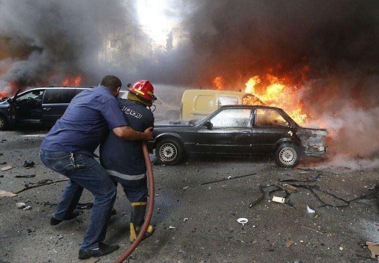 A firefighter is helped as he extinguishes fire at the site of an explosion in Beirut's southern suburb of Bir al-Abed on July 9, 2013