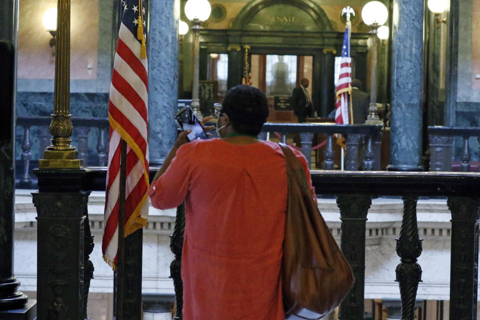 Rep. Sonya Williams-Barnes, D-Gulfport, takes a smartphone photograph of the American flag and the empty slot adjacent to it where the former Mississippi state flag rested in the hallway of leading to the legislative chambers, Wednesday, July 1, 2020 at the Capitol in Jackson, Miss. The flags were quietly removed during the day. Gov. Tate Reeves signed a bill on Tuesday that retired the last state flag with the Confederate battle emblem. Upon his signature to the bill, the flag was no longer the official banner. (AP Photo/Rogelio V. Solis)