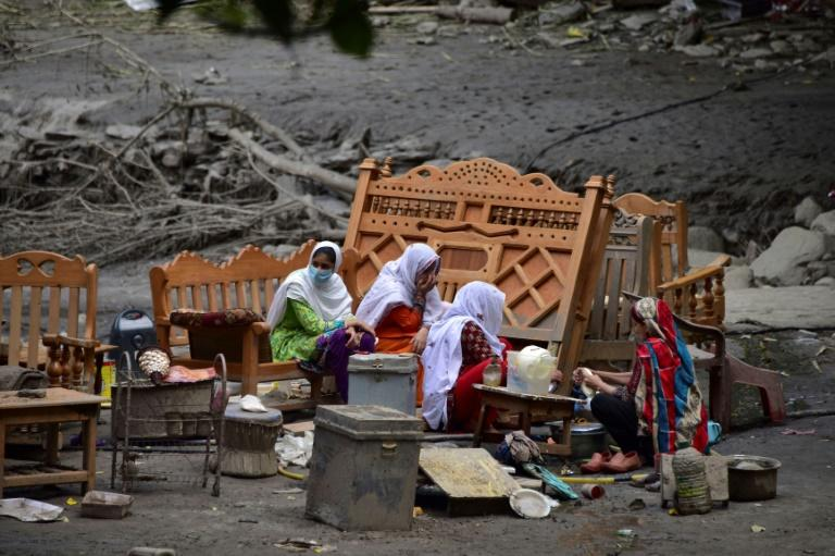 A Pakistani Kashmiri family gather around their belongings outside their damaged house following heavy monsoon rains in Neelum valley, near the Line of Control in Pakistan-controlled Kashmir