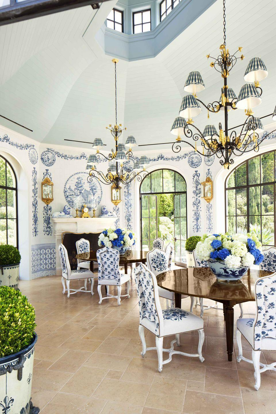 """<p>A fantasy in blue and white, the dining pavilion of a Los Angeles home by designer <a href=""""https://www.anthonybaratta.com"""" rel=""""nofollow noopener"""" target=""""_blank"""" data-ylk=""""slk:Anthony Baratta"""" class=""""link rapid-noclick-resp"""">Anthony Baratta</a> has ceilings painted in two lively shades of blue that accentuate the room's soaring height. The walls are covered in fanciful tiles from <a href=""""https://www.solarantiquetiles.com"""" rel=""""nofollow noopener"""" target=""""_blank"""" data-ylk=""""slk:Solar Antique Tiles"""" class=""""link rapid-noclick-resp"""">Solar Antique Tiles</a>. </p>"""