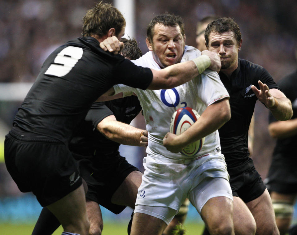England's Steve Thompson, centre, is by tackled by New Zealand's Jimmy Cowan, left, and Tony Woodcock during their international rugby union match at Twickenham stadium in London, Saturday, Nov. 21, 2009. (AP Photo/Odd Andersen)