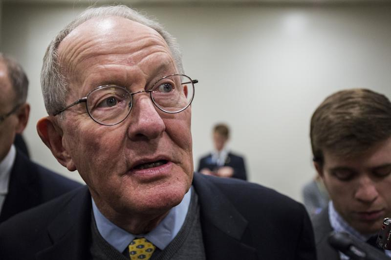 Sen. Lamar Alexander (R-Tenn.) speaks to the media Wednesday while heading to a roll call vote on Capitol Hill.