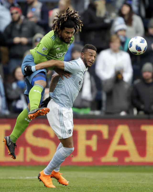 Seattle Sounders defender Roman Torres, left, heads the ball over Sporting Kansas City forward Khiry Shelton, right, during the first half of an MLS soccer match in Kansas City, Kan., Sunday, April 15, 2018. (AP Photo/Orlin Wagner)