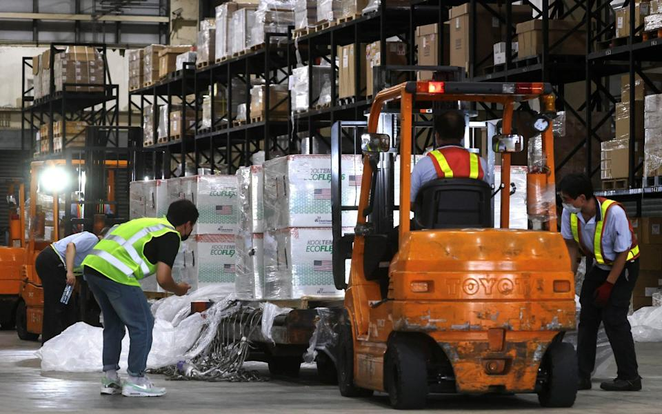 Workers transport Moderna vaccines shipped from the US to Taiwan Air Cargo Terminal in Taoyuan - Reuters