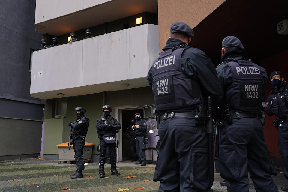 <p>Heavily-armed police stand outside an apartment building in Kreuzberg district during raids in which police arrested three suspects</p>Getty Images
