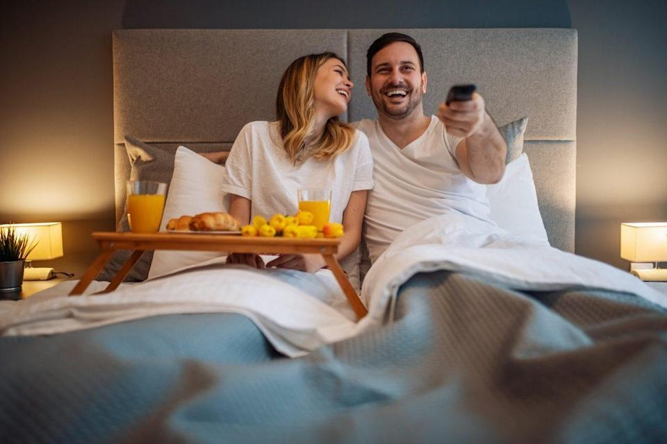 Happy couple having a breakfast in the bed.Romantic moments at home.They are watching tv in bedroom.