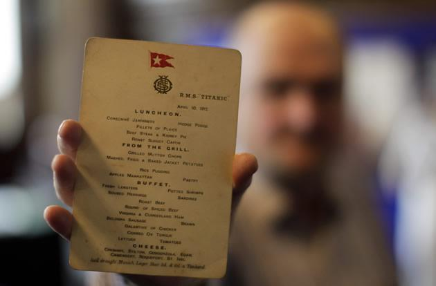 A member of staff from the Auction house Aldridge and Son holds an original Titanic menu.