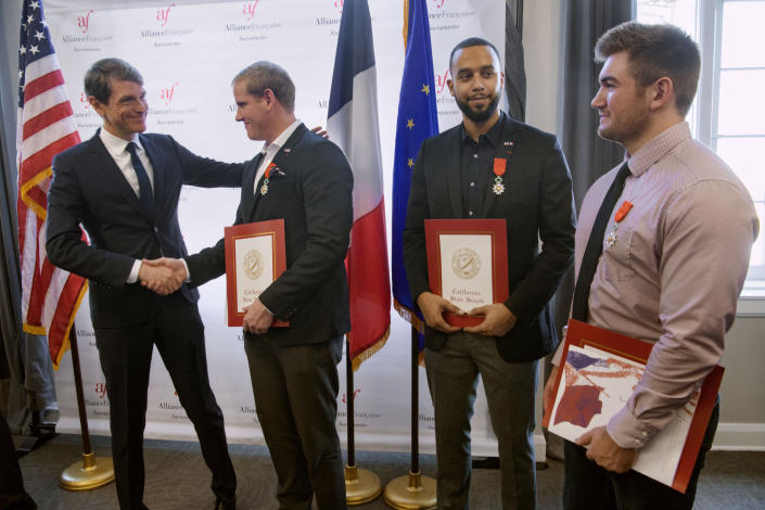 French Consul General Emmanuel Lebrun-Damiens, left, congratulates Spencer Stone, Anthony Sadler, and Alek Skarlatos during a French Naturalization Ceremony in Sacramento, Calif., Thursday, Jan. 31, 2019. The three men were heralded as heroes when they subdued an armed terrorist on a train in France in 2015. Today they were granted French citizenship. (AP Photo/Randall Benton)