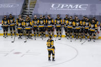 Pittsburgh Penguins' Sidney Crosby, foreground, skates back to teammates during a ceremony honoring his 1000th NHL hockey game with the team before an NHL hockey game against the New York Islanders, Saturday, Feb. 20, 2021, in Pittsburgh. . (AP Photo/Keith Srakocic)