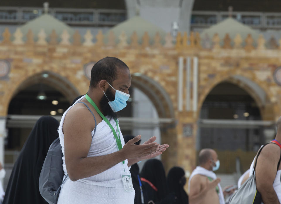 A Muslim pilgrim prays in front of the the Kaaba, the cubic building at the Grand Mosque, as he wears a mask and keeps social distancing, a day before the annual hajj pilgrimage, Saturday, July 17, 2021. The pilgrimage to Mecca required once in a lifetime of every Muslim who can afford it and is physically able to make it, used to draw more than 2 million people. But for a second straight year it has been curtailed due to the coronavirus with only vaccinated people in Saudi Arabia able to participate. (AP Photo/Amr Nabil)