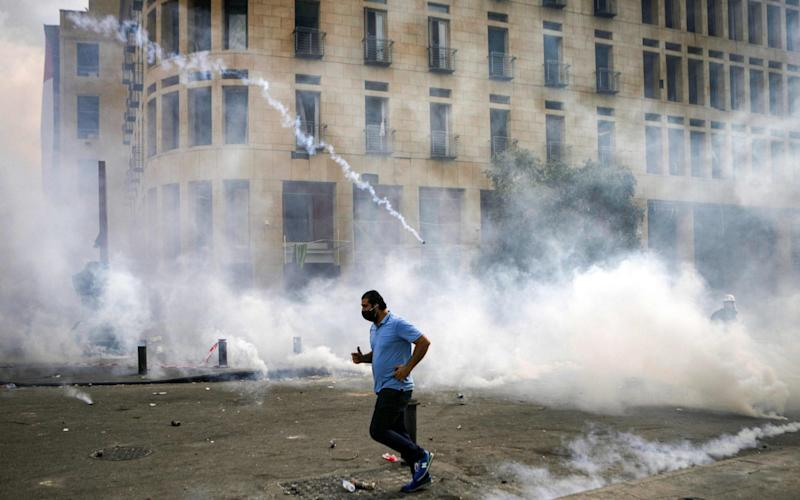 A Lebanese protester runs for cover from tear-gas fired by security forces during clashes in downtown Beirut following demonstrations over the explosion which ripped through the city - Patrick Baz /AFP