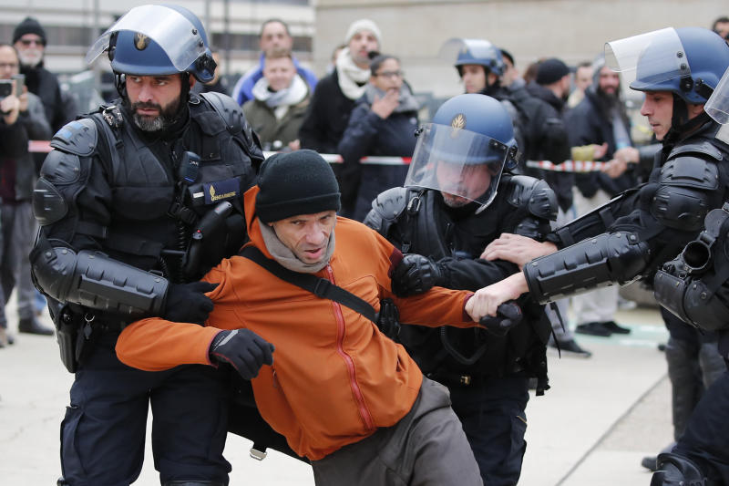 Riot police officers detain a striking train worker outside the the Gare de Lyon train station, Monday, Dec. 23, 2019 in Paris. A wildcat protest comes on Day 19 of nationwide strike over the government's plans to raise the retirement age to 64. The union-led protest Monday led to a standoff with riot police that spilled onto the streets around the historic Gare de Lyon train station. (AP Photo/Francois Mori)