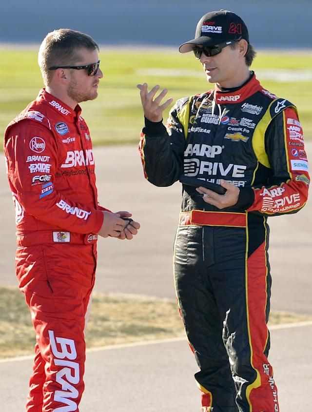 Jeff Gordon, right, talks with Justin Allgaier before qualifying for the NASCAR Sprint Cup Series auto race at Chicagoland Speedway in Joliet, Ill., Friday, Sept. 13, 2013. (AP Photo/Nam Y. Huh)
