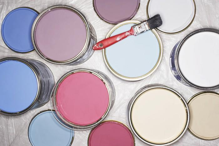 Buckets of paint, with a paintbrush on top of one of them, laid out on the floor.