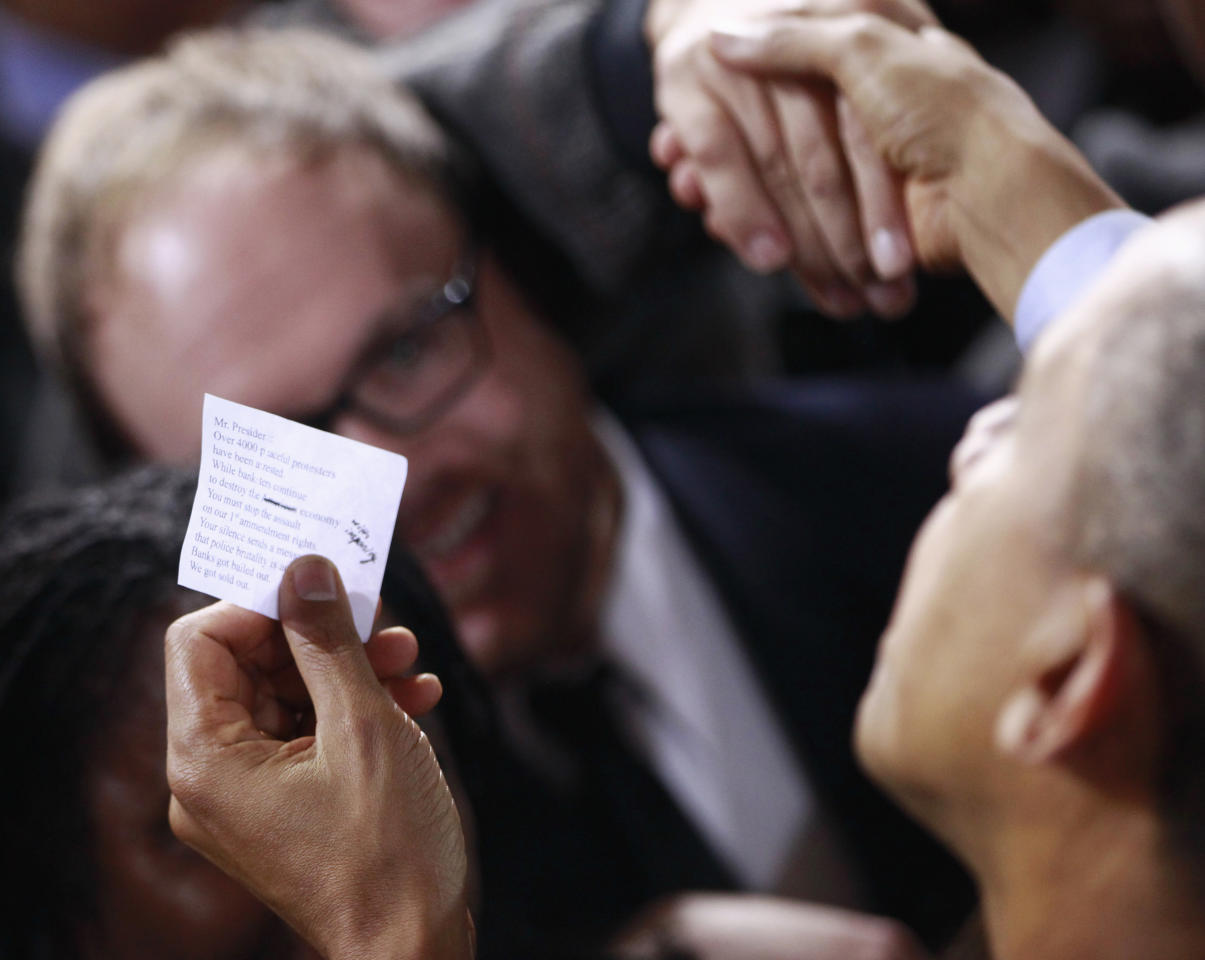A protester, wearing glasses, smiles as he hands President Barack Obama a note as the president greeted audience members after speaking about jobs, Tuesday, Nov. 22, 2011, at Manchester High School Central in Manchester, N.H. (AP Photo/Charles Dharapak)