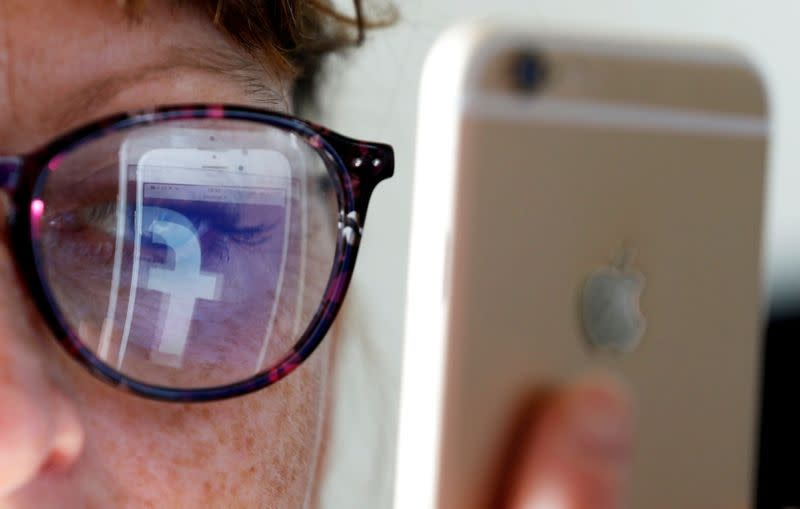 FILE PHOTO: The Facebook logo is reflected on a woman's glasses in this photo illustration