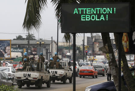 A U.N. convoy of soldiers passes a screen displaying a message on Ebola on a street in Abidjan